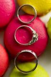 银婚圆环和定婚戒指在蛋白杏仁饼干 图库摄影