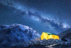 银河、黄色发光的帐篷和山 库存图片
