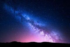 银河和桃红色光在山 夜五颜六色的风景 免版税库存图片