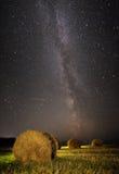 银河和麦田与干草堆 免版税库存图片