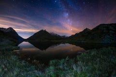 银河弧和满天星斗的天空的卓著的秀丽在湖反射了在阿尔卑斯的高处 Fisheye风景dist 免版税库存图片