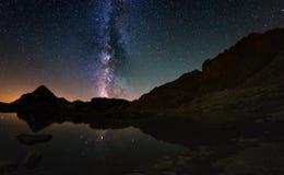 银河弧和满天星斗的天空的卓著的秀丽在湖反射了在阿尔卑斯的高处 Fisheye风景dist 免版税库存照片