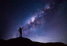 银河风景 指向明亮的星的愉快的妇女剪影 免版税库存图片