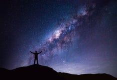 银河风景 站立在与夜空和明亮的星的山顶部的愉快的人剪影在背景 免版税库存图片