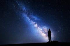银河 一个人的夜空和剪影 免版税图库摄影