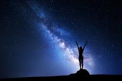 银河 一个常设女孩的夜空和剪影 库存照片