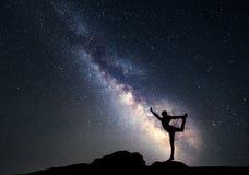 银河 一名运动的妇女的夜空和剪影 免版税库存图片