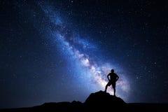 银河 与一个人的星和剪影的夜空 免版税库存照片