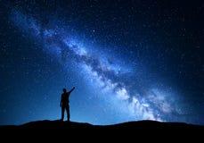 银河 指向在夜满天星斗的天空的一个常设人的剪影手指在山 库存照片