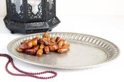 银盘特写镜头用日期果子、念珠和装饰黑暗的摩洛哥,阿拉伯灯笼在白色桌上 库存照片