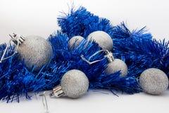 银色发光的圣诞节球和发光的蓝色磁带在白色背景 免版税库存图片