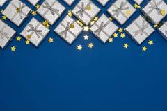银色发光的礼物和金黄星边界在蓝色背景 免版税库存图片