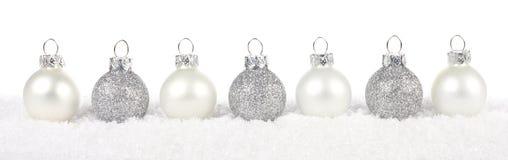 银色和白色圣诞节在雪的中看不中用的物品边界在白色 免版税库存照片