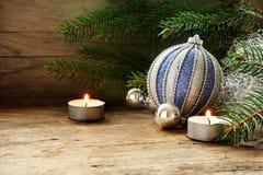 银色和蓝色中看不中用的物品、冷杉分支和蜡烛作为圣诞节d 库存图片