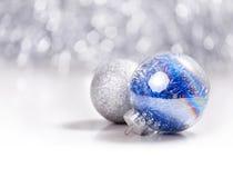 银色和蓝色圣诞节装饰在闪烁bokeh背景的球与文本的空间 Xmas和新年好 免版税库存图片