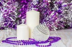 银色圣诞节球、两个白色蜡烛和紫色小珠 库存图片