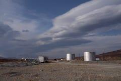 银色坦克和天空与双突透镜的云彩 图库摄影