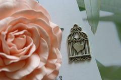 银色垂饰,在一只笼子的心形的护身符在开花的背景上升了 免版税库存图片