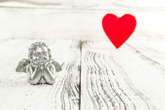 银色天使和红色心脏在白色木背景 免版税库存图片