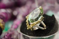 银色定婚戒指宏观射击与绿色紫色的宝石的,在五颜六色,闪耀的背景 库存照片