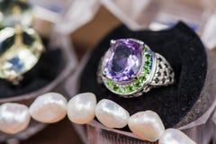 银色定婚戒指宏观射击在礼物盒的在五颜六色,闪耀的背景 免版税库存图片