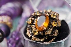 银色定婚戒指宏观射击在礼物盒的在五颜六色,闪耀的背景 免版税图库摄影