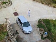 银色斜背式的汽车汽车、走的人和饮水机在正方形,顶视图 创造性的空中照片,与拷贝的路面 免版税图库摄影