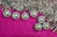 银色新年的和圣诞装饰在桃红色基地 免版税库存照片