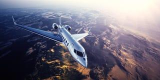 银色普通飞行在山的设计私人喷气式飞机现实照片  与太阳的空的蓝天在背景 免版税库存图片