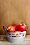 银色桶在木桌上的红色苹果。 库存照片