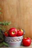 银色桶在木桌上的红色苹果 免版税库存图片