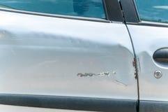 银色汽车的损坏的门有被抓的和被剥皮的油漆的在崩溃事故和碰撞接近  免版税库存照片