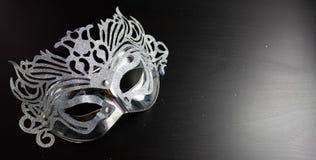 银色狂欢节面具,安置在黑背景 免版税库存照片