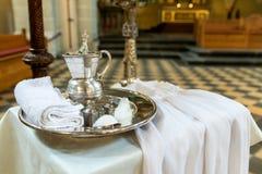 银色盘子和水罐有水辅助部件和礼服的孩子的洗礼的符合教会传统 图库摄影