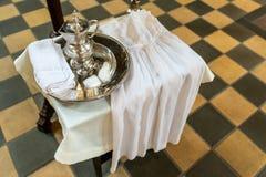 银色盘子和水罐有水辅助部件和礼服的孩子的洗礼的符合教会传统 免版税库存图片