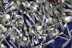 银色碗筷的附聚在蓝色天鹅绒背景的 库存图片