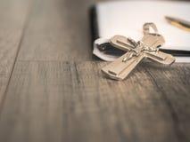 银色耶稣受难象和一支笔在一个空白的笔记本,基督徒 免版税库存照片