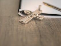 银色耶稣受难象和一支笔在一个空白的笔记本,基督徒 免版税库存图片