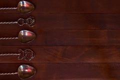 银色茶匙被安排在黑暗的木桌 图库摄影