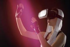 银色衣裳的一个女孩有敞篷的调查虚拟现实 免版税库存照片