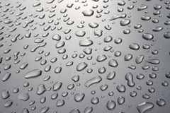 银色表面上的雨珠 免版税库存图片