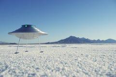 银色金属飞碟飞碟苛刻的白色沙漠行星风景 免版税库存照片