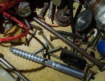 银色钉子和螺丝在木纹理 免版税库存图片
