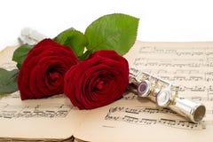 银色长笛和美丽的红色玫瑰在一个古老音乐比分 免版税库存照片