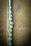 银色长笛有老钢背景 免版税库存图片