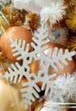 银色闪烁雪花塑造了与许多金铺砂机球形的装饰品的圣诞节装饰品 免版税库存图片