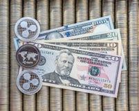 银色隐藏硬币起波纹XRP,纸笔记美元 金属硬币在光滑的背景中互相被计划,特写镜头vi 免版税库存图片