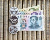 银色隐藏硬币起波纹XRP,纸衡量单位中国人元 金属硬币在光滑的背景中互相被计划, c 免版税库存图片