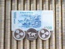 银色隐藏硬币起波纹XRP,纸衡量单位韩语被赢取 金属硬币在光滑的背景中互相被计划,克洛 库存图片