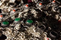 银色首饰腹网与绿色和红色宝石的 免版税库存照片